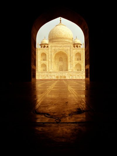 A photo of the Taj Mahal as seen through an arched window