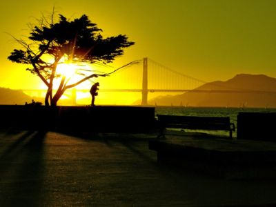 A silhouetted man stand in front to the Golden Gate Bridge at sunset