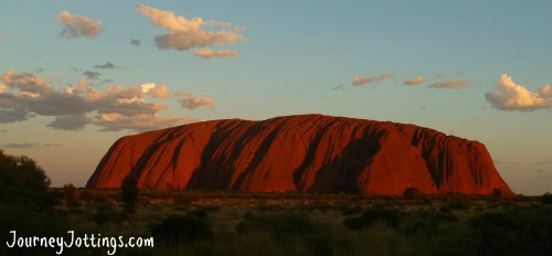 A distant photo of Uluru at sunset taken from across the plains