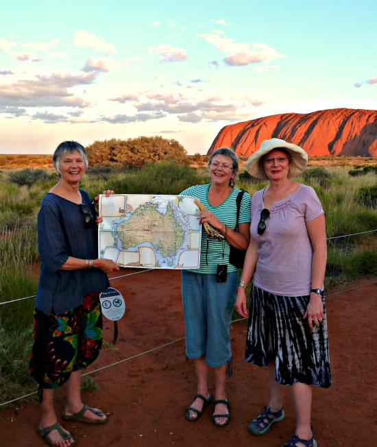 3 visitors hold up a map of Australia showing Uluru situated in the very centre - An Uluru Fact