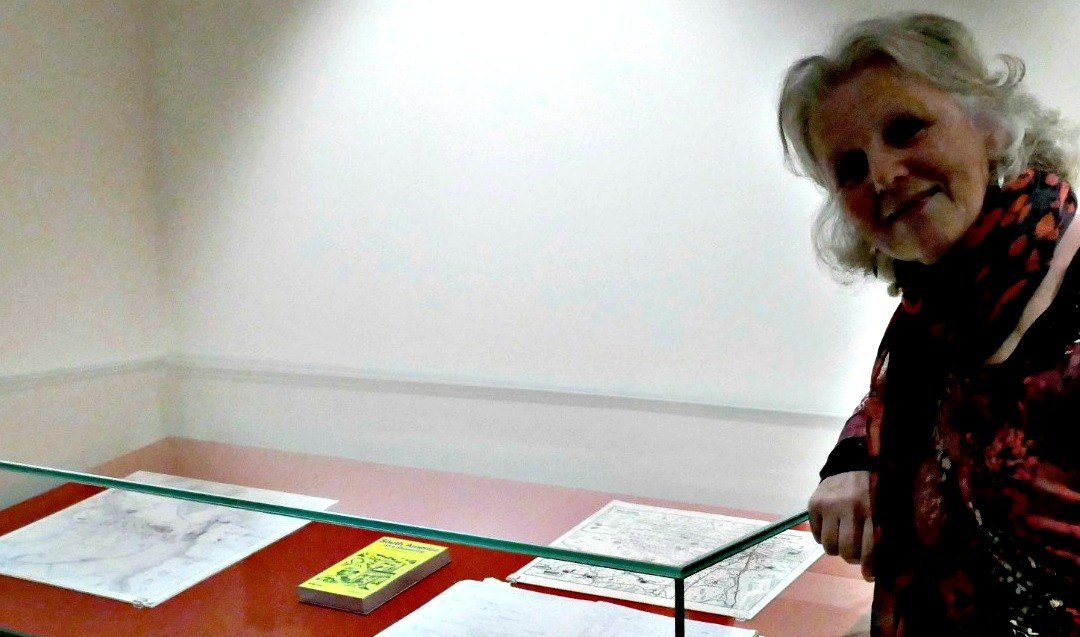 Linda fairbairn standing beside her map of Central Australia, alongside Tolkein's Mordor