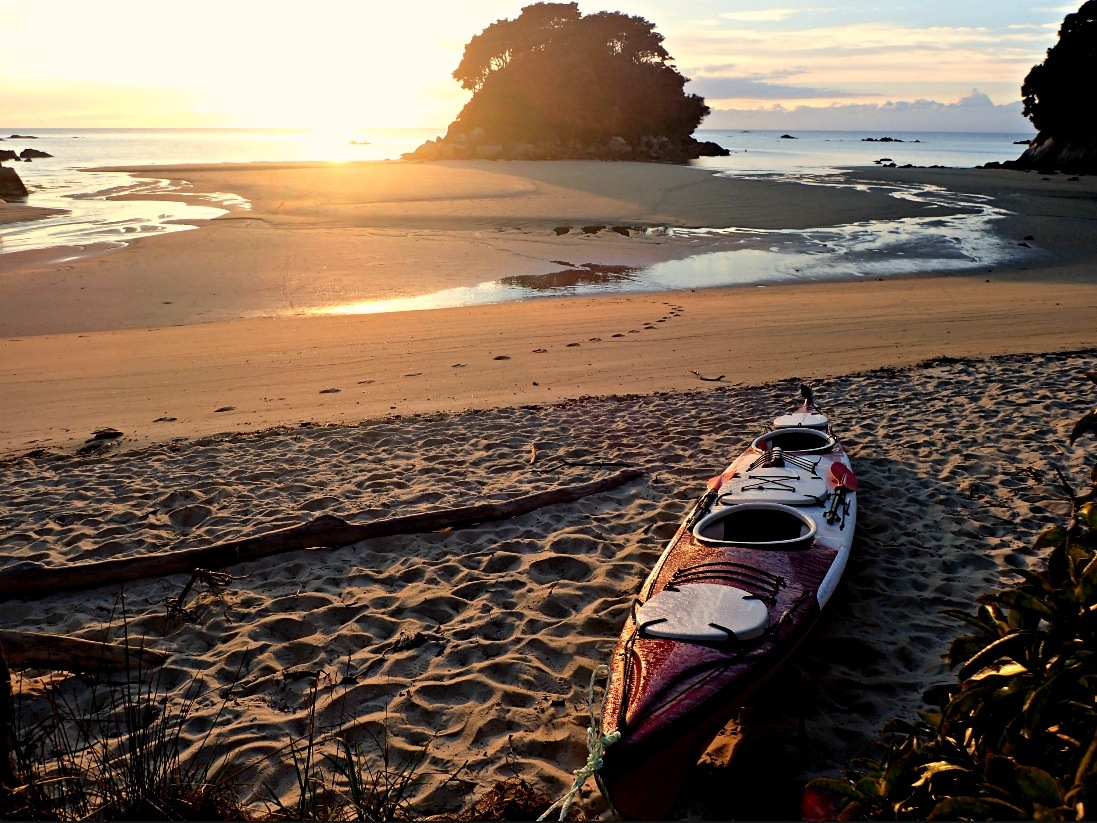Kayak pulled up on the beach at Mosquito Bay and the first rays of sunshine hitting it