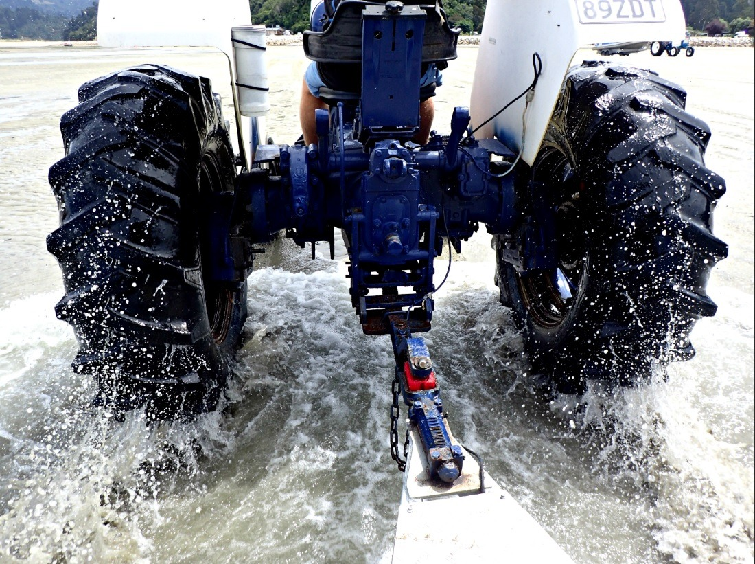 Tractor wheels spraying up sea water as it tows a trailer full of kayaks in